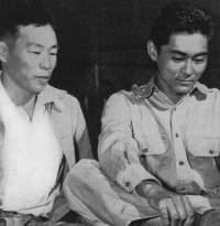 Mitsuru Doi, one of Kauai's first volunteers tries on newly issued boots while his father looks on.  [U.S. Army Signal Corps]