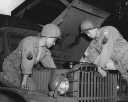 Camp McCoy, WIS - 100th Bn. Soldiers Torantsugu Ryusaki (left) and Masao Uehara (right) Assigned to motor pool. Both working on a GMC army truck. Note: Insignia of the ARMY ground forces reserve.  [U.S. Army Signal Corps]