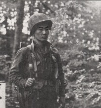 Sgt. James Kawashima (Honolulu) standing guard near Co. B command post at Bruyeres, France.  [U.S. Army Signal Corps]