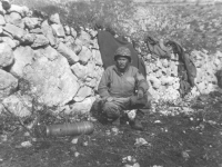 A soldier squats next to a mortar shell in Italy, 1944. [Courtesy of Mary Hamasaki]