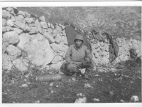 A soldier squats next to a mortar shell in Italy. [Courtesy of Mary Hamasaki]