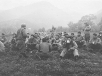 Soldiers sit on a hill and enjoy coffee and music. [Courtesy of Mary Hamasaki]