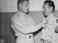 Technician 4th class Kenichi Suehiro (100th HQ) of Honolulu stands proudly as he receives his medal. [U.S. Army Signal Corps]
