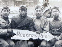 """5 soldiers at pier holding sign """"Rookery Road"""".  Kazuo Yamane seated on the far right.  [Courtesy of James Nogawa]"""