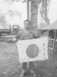 Tom Matsumura holds a Japanese sword and flag while stationed in the Philippines [Courtesy of Florence Matsumura]