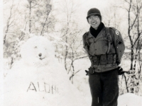 "(December 1942) ""Note fingers sticking out of my pockets are my gloves, and on the snow bear reads ALOHA."" Eugene Kawakami is standing in the snow wearing his G-I glasses and muffler made for him by his wife, Gladys.  [Courtesy of Joanne Kai]"