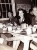 "(November 1942) ""Thanksgiving Day Party – Left to Right: S/Sgt. Kawakami, S/Sgt. Nishida, Miss Alice Kenny of Sparta USO, and 1st/Sgt. Nakamura. (Note Chow on Table)."" Eugene Kawakami is seated on the left.   [Courtesy of Joanne Kai]"
