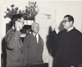 Jack Mizuha, Associate Justice of the Hawaii Supreme Court, swearing in his friend Takashi Kitaoka as the newly appointed judge for the Second Circuit Court on Maui in 1962.  The two men were both born on Maui and were original members in the 100th Infantry Battalion. [Courtesy of Takashi Kitaoka]