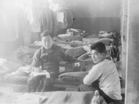 Taken on the morning of Sept 4, 1942 in the barracks - Camp McCoy, WIS. Sun-writing a letter - listening to the radio pictured with Pvt. N. Higa.  [Courtesy of John Oki]