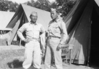 Mits Fukuda standing in front of his tent at Camp McCoy with Sparky Matsunaga [Courtesy of David Fukuda]