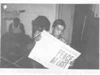 "Moriso Teraoka holds up a newspaper reading ""Peace at Last"" on V-J day while in Leghorn, Italy, 1945 (Courtesy of Moriso Teraoka)"