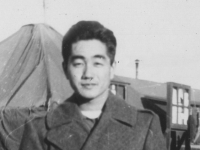 Taken Sept. 23, 1942  at Camp McCoy camp just before going to a show.   The show house is just back of the tent in the background but it was so cold we had to wear our overcoat to attend it.  Coat sleeve is a little too long.  We moved from there to our new camp site the follwing day into barracks.  [Courtesy of Jan Nadamoto]