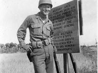 James Funakoshi poses by a warning sign at 100th Battalion camp in Italy [Courtesy of Robert Arakaki]