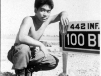 Tamura poses with the 442nd/100th Battalion sign in Italy [Courtesy of Robert Arakaki]
