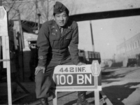 Ernest Kanno poses with his Battalion's sign in Italy [Courtesy of Robert Arakaki]