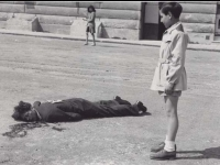 "Italian boy looks on at dead ""Collaborator"" killed in Milan Park, 1945. [Courtesy of Fumie Hamamura]"