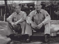 Ralph Fukunaga and Stanley Hamamura sit in front of building. [Courtesy of Fumie Hamamura]
