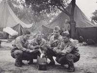 Kaoru Naito, Calvin Shimogaki, Suyeoshi and Hisashi Komori warming themselves by a fire at Camp McCoy in June 1942. [Courtesy of Fumie Hamamura]