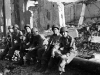 Soldiers take a rest while marching through a bombed out Italian city [Courtesy of Carol Inafuku]