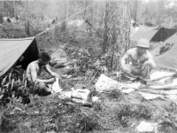 "'Toro' John Kihara and 'Old Man' Tanaka cleaning their rifles in front of tents at Camp Shelby [Courtesy of Leslie Taniyama] Inscription: Louisiana April '43 Maneuvers ""Toro"" John Kihara, ""Old Man""  Tanaka. both deceased"