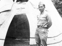 Tokuji Ono standing with hands behind his back in front of an Indian teepee at Stand Rock [Courtesy of Leslie Taniyama] Inscription: Reverse: 7-5-42 'Yours Truly', Bullie. At 'Stand Rock', Winnebago Indian ceremonial ground on the Wisconsin River