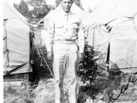 William Takaezu posing in front of tents at Camp Shelby, Mississippi. [Courtesy of Mrs. William Takaezu]