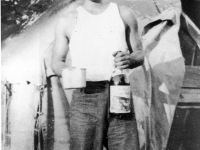 Richard Yoneshige at Camp Shelby with a bottle of wine [Courtesy of Ukichi Wozumi]