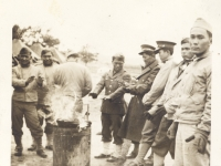 Shinyei Nakamine (far right) and other soldiers warm themselves by the fire at Camp McCoy, Wisconsin. (Courtesy of Anita Korenaga)
