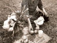 Mrs. Ushi Nakamine offering tangerines for her son, Shinyei, at the Punchbowl Cemetary (Courtesy of Anita Korenaga)