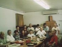 B Company chapter meeting in clubhouse sent to Takeshi Teshima. Sitting around the table from left: Robert Takashige, Thomas Tsubota, Rikio Tsuda, Mrs. Rikio Tsuda, Mrs. Hajime Kodama, Mrs. Sonsei Nakamura, Joichi Muramatsu, Mrs. Raymond Nosaka, Raymond Nosaka.  Standing from left to right:  Mrs. Bernard Akamine, Mrs. Robert Arakaki, Robert Arakaki, Joyce Muramatsu Doi, Bernard Akamine, Drusilla Akamine Tanaka. [Courtesy of Ted Teshima]