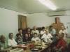 B Company chapter meeting in clubhouse sent to Takeshi Teshima. Sitting around the table from left: Robert Takashige, Thomas Tsubota, Rikio Tsuda, Mrs. Rikio Tsuda, Mrs. Hajime Kodama, Mrs. Sonsei Nakamura, Joichi Muramatsu, Mrs. Raymond Nosaka, Raymond Nosaka.  Standing from left to right:  Mrs. Bernard Akamine, Mrs. Robert Arakaki, Robert Arakaki, Joyce Muramatsu Doi, Bernard Akamine, Drusilla Akamine Tanaka. [Courtesy of Ted Teshima]