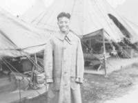 Joe Nakahara in his trenchcoat at Camp McCoy, Wisconsin, 1942. [Courtesy of Velma Nakahara]