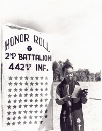Protestant Chaplain Hiro Higuchi, Waipahu, Oahu, T.H., reads the names on the roll; each name represented by a star on the banner by which he stands.  These 71 men represent the deaths in the 2nd battalion, 442 Infantry, made up of Americans of Japanese descent, that went into action in Italy, June 26, 1944. [U.S. Army Signal Corps]