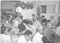 Col. Turner (sitting, far right), listens to Mits Fukuda (standing) at a postwar dinner in Hawaii. [Courtesy of Bob Kainuma]